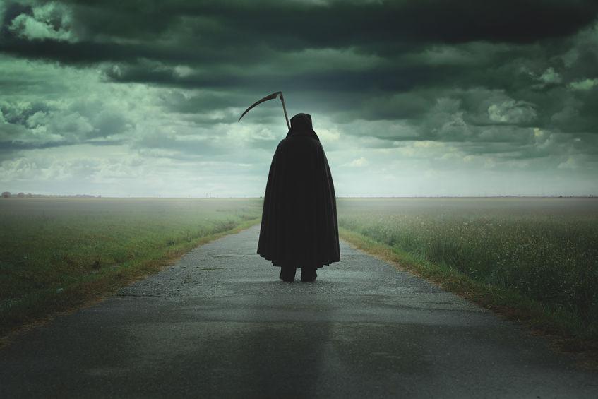 grim reaper walking on a dark desolate road .halloween and death